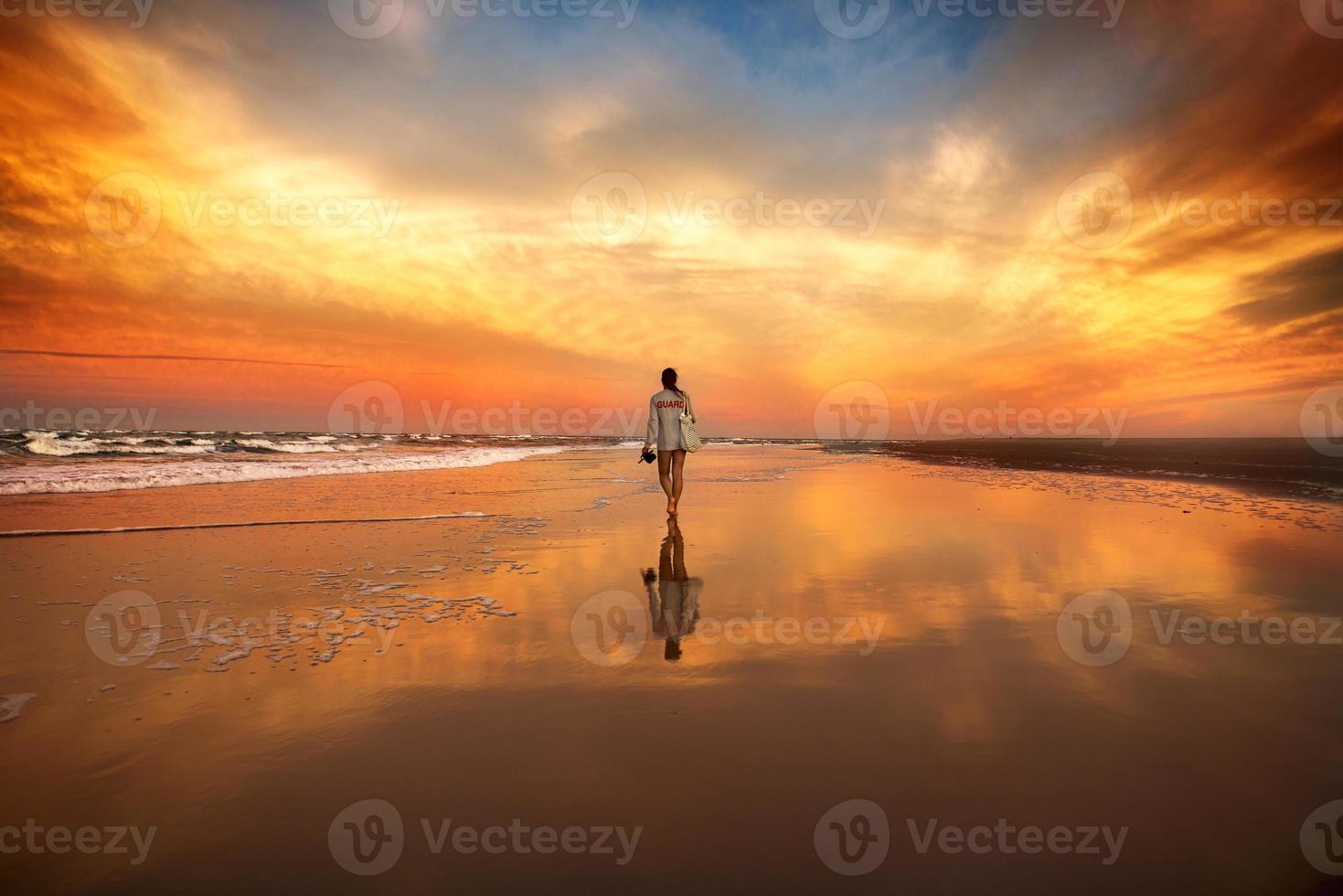mulher caminhando na praia perto do mar ao pôr do sol foto