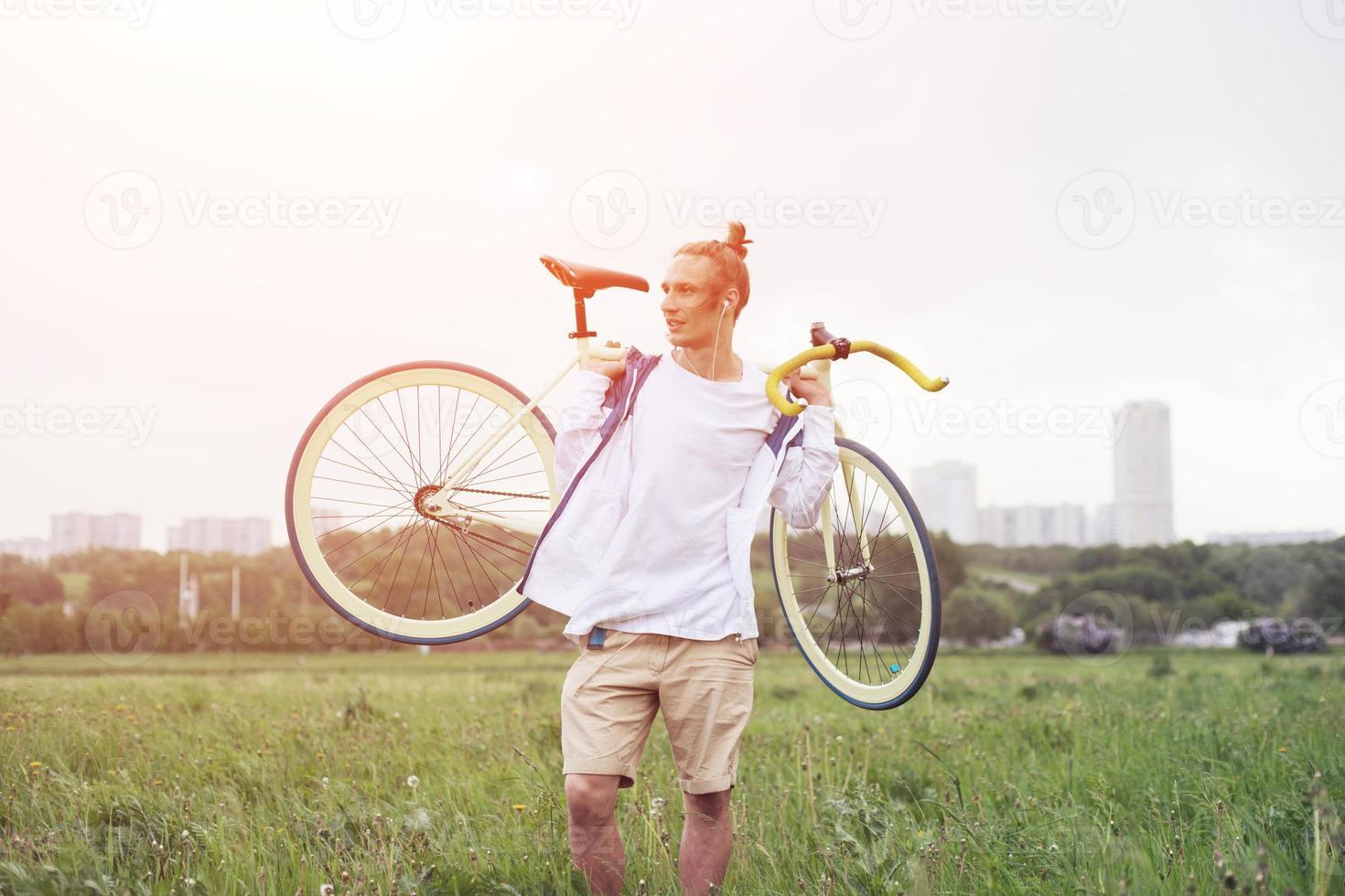 homem sorridente na camiseta em branco andando com bicicleta foto