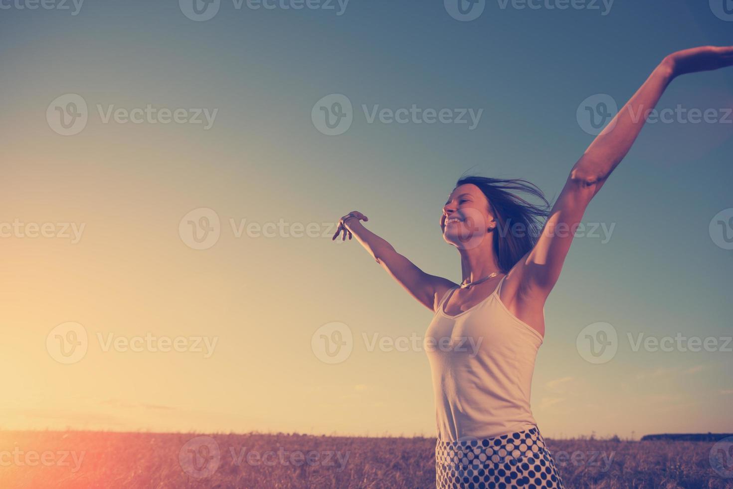 garota, apreciando o pôr do sol no campo foto
