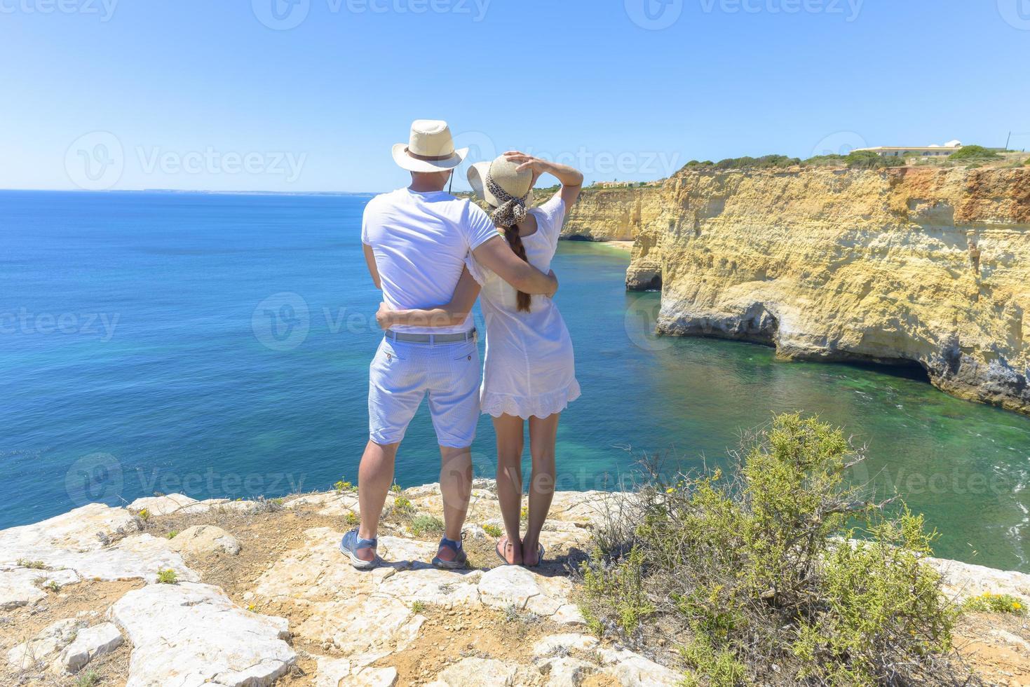 casal apreciando a vista para o mar de um penhasco foto