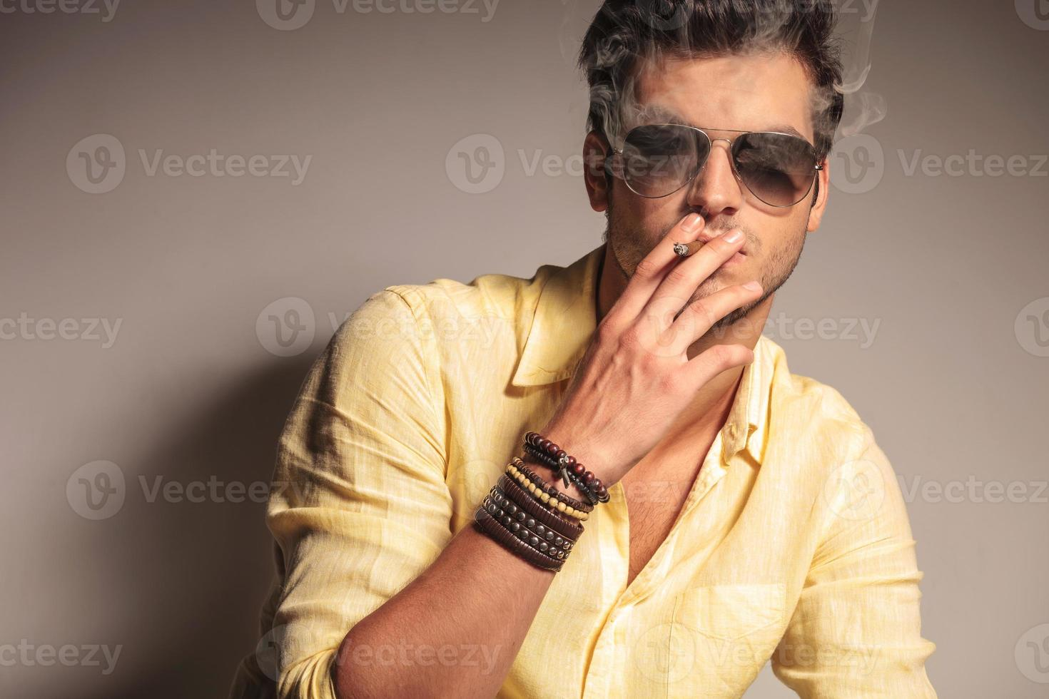 homem legal moda com óculos de sol, desfrutando de seu cigarro foto