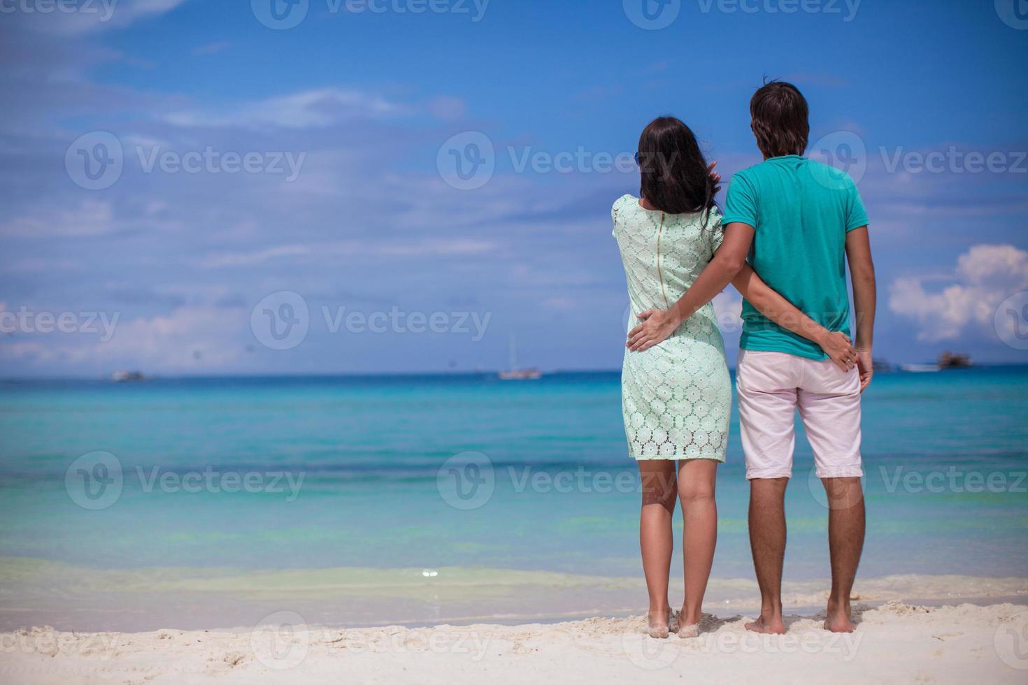 jovem casal amando um ao outro na praia de areia branca foto
