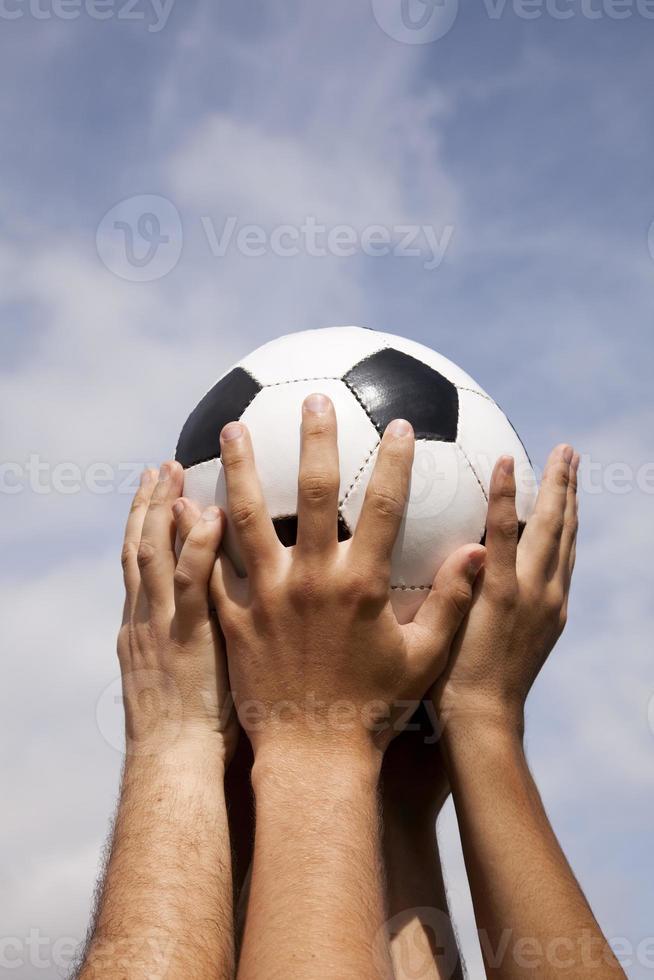 mãos segurando uma bola de futebol no ar foto