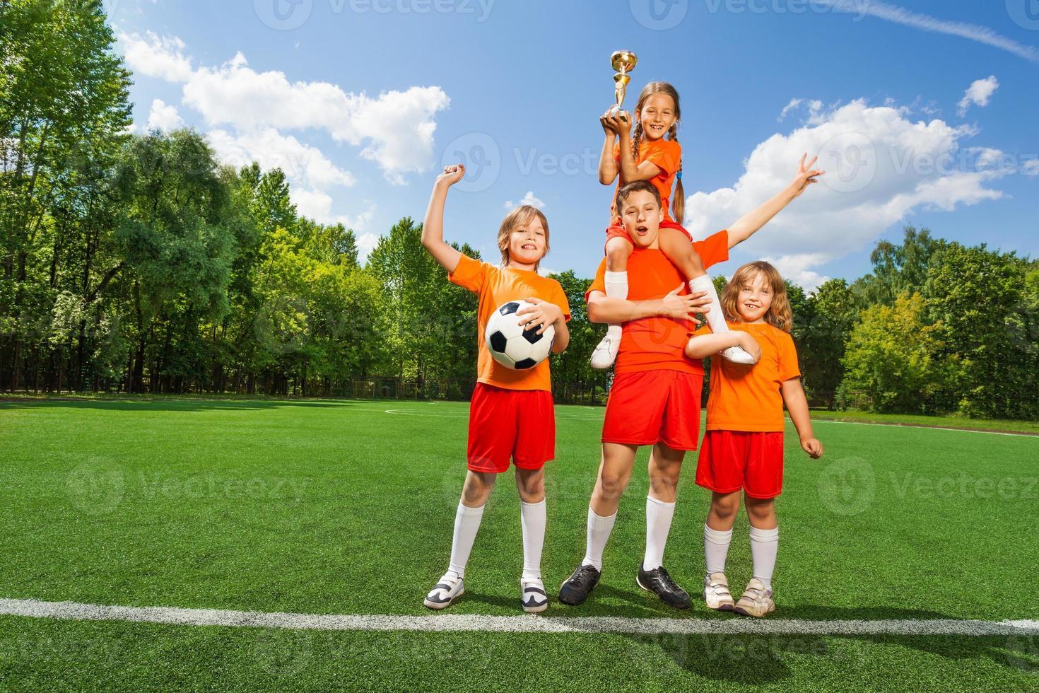 crianças felizes com copo de ouro ficar na pirâmide foto