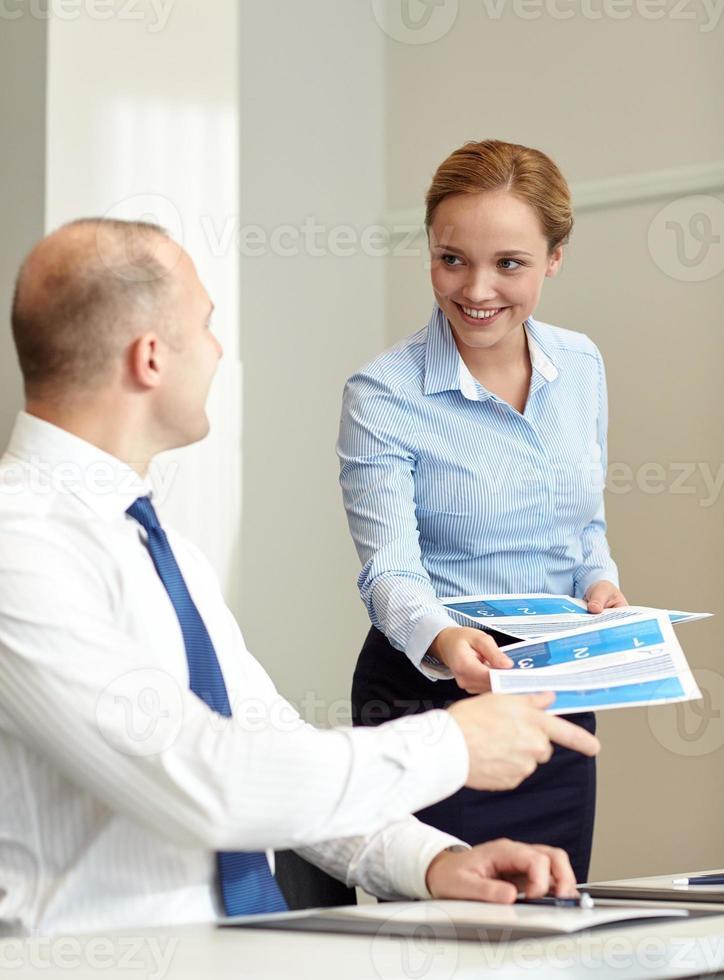 mulher sorridente dando papéis para homem no escritório foto