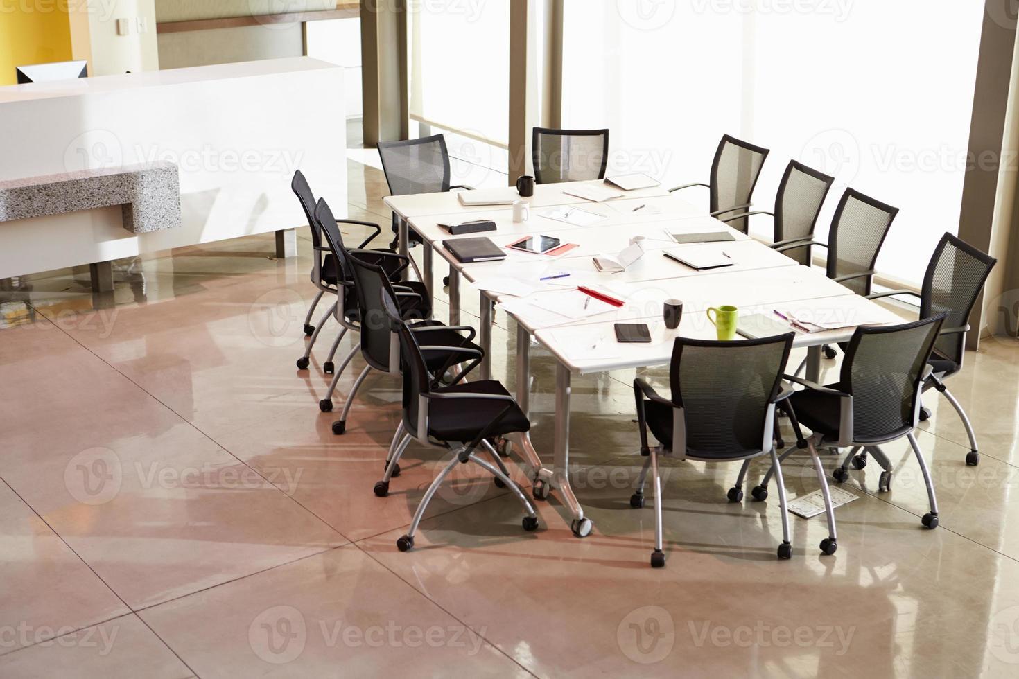 cadeiras dispostas em torno da mesa da sala de reuniões vazia foto