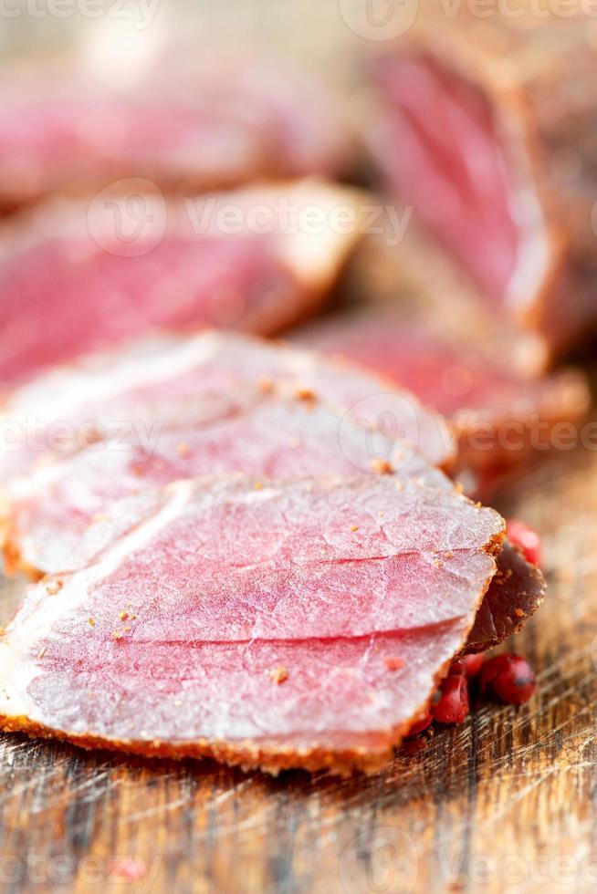 fatias de carne curada e pimenta na mesa close-up foto