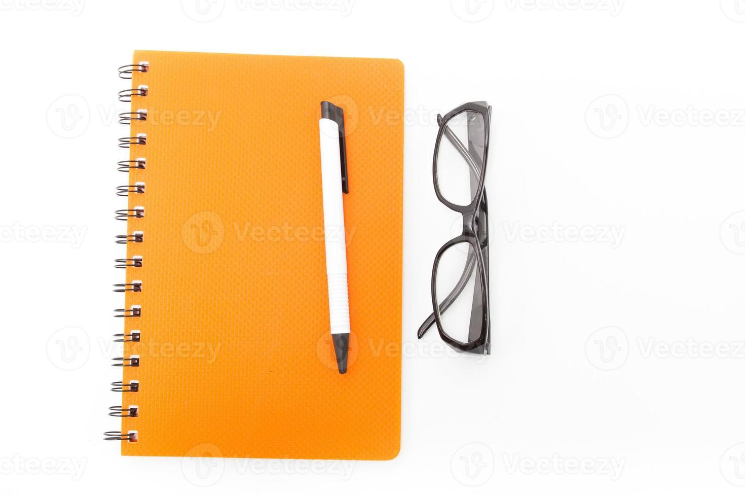 caderno e caneta com óculos foto