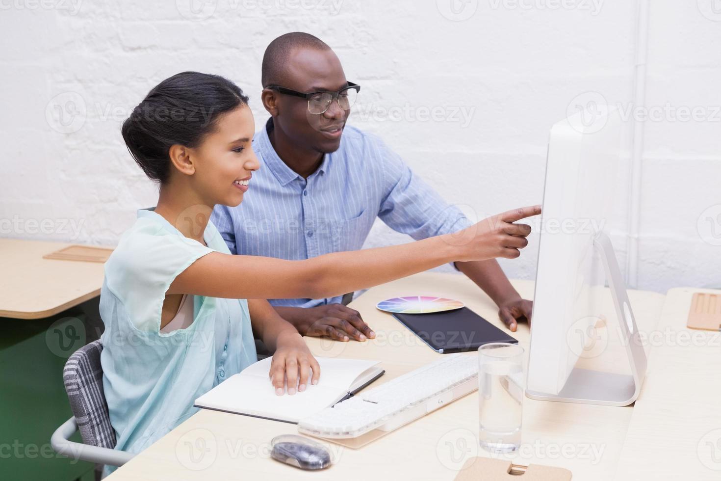 mulher mostrando algo para seu colega no laptop foto