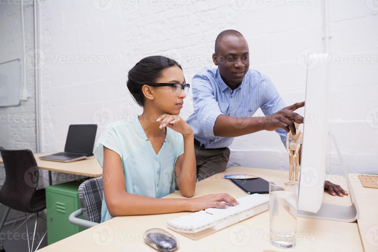 homem mostrando algo para seu colega no laptop foto