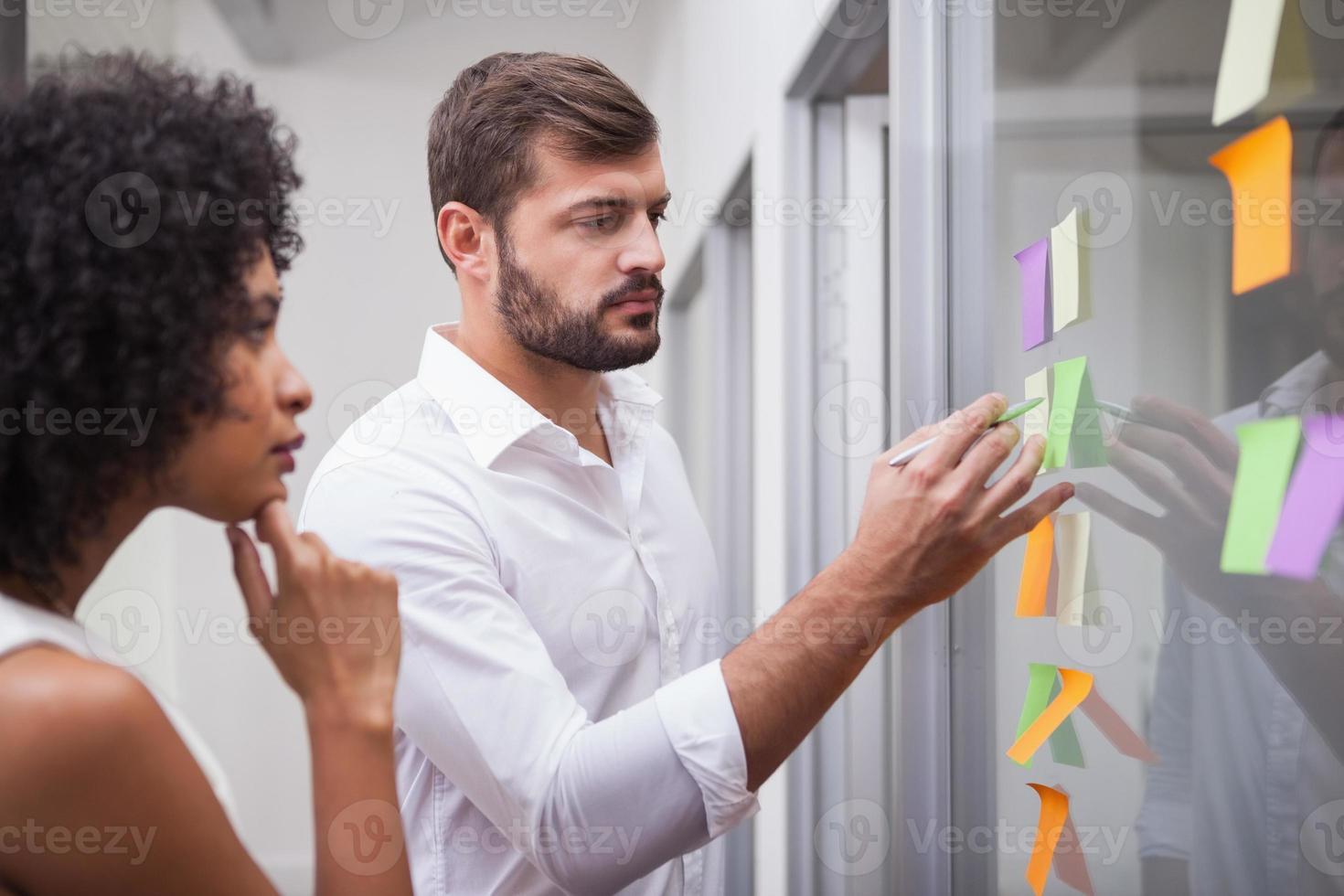 equipe de negócios casuais olhando notas autoadesivas foto