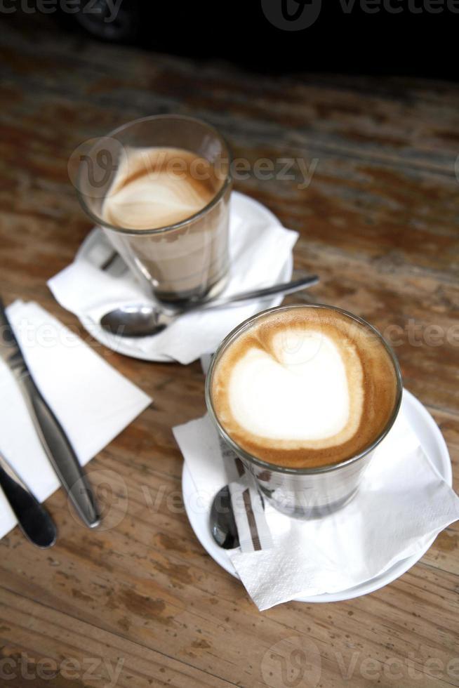 café e talheres com espuma em forma de coração foto