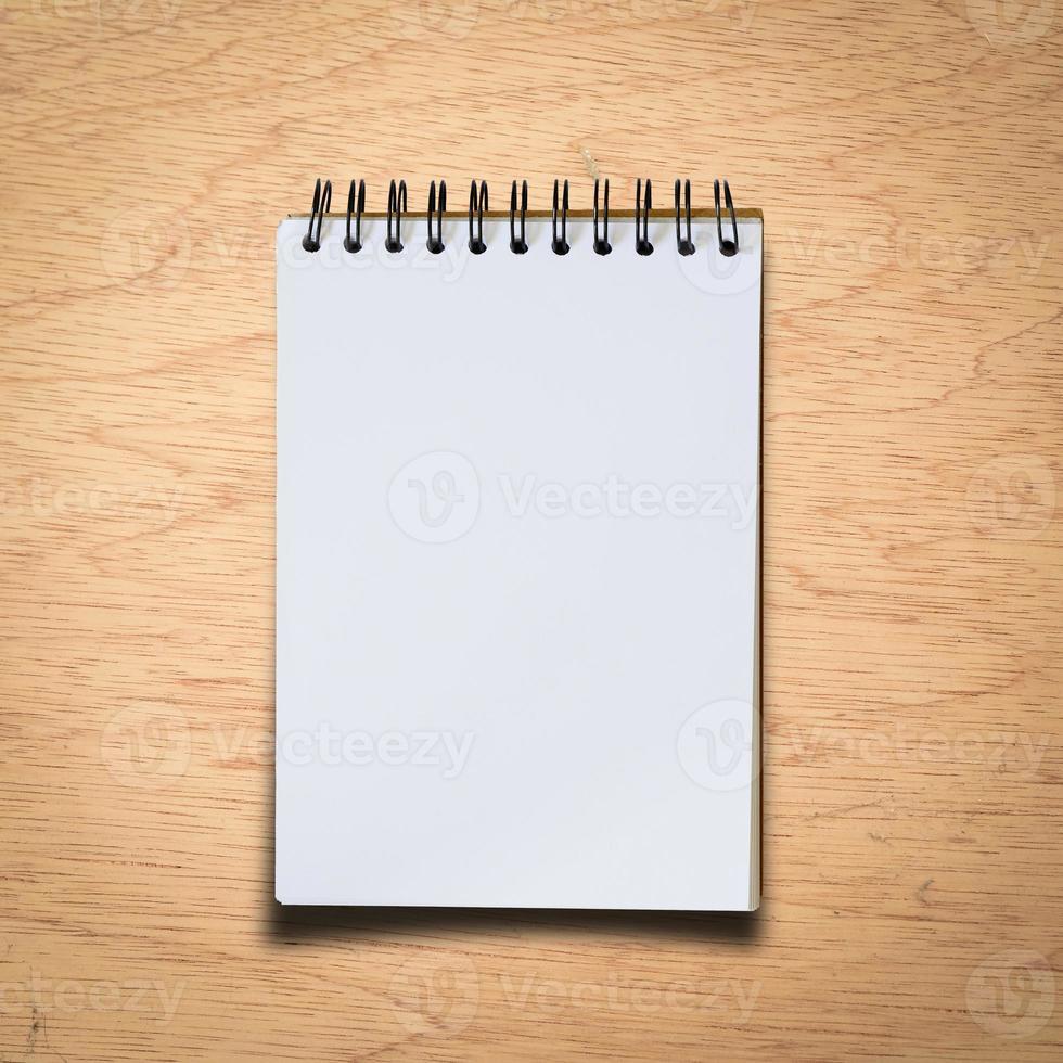 caderno preto sobre um fundo de madeira com traçado de recorte foto