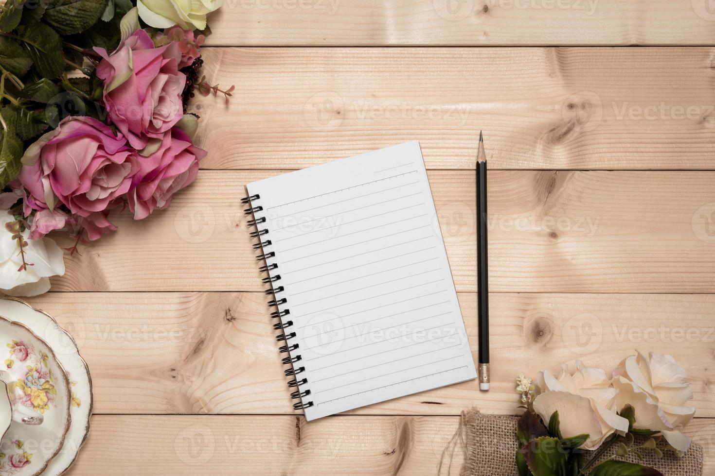 bloco de notas com lápis sobre o fundo de madeira foto