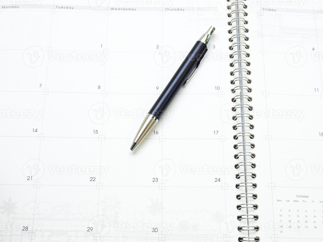 página de calendário no organizador e uma caneta como plano de fundo foto