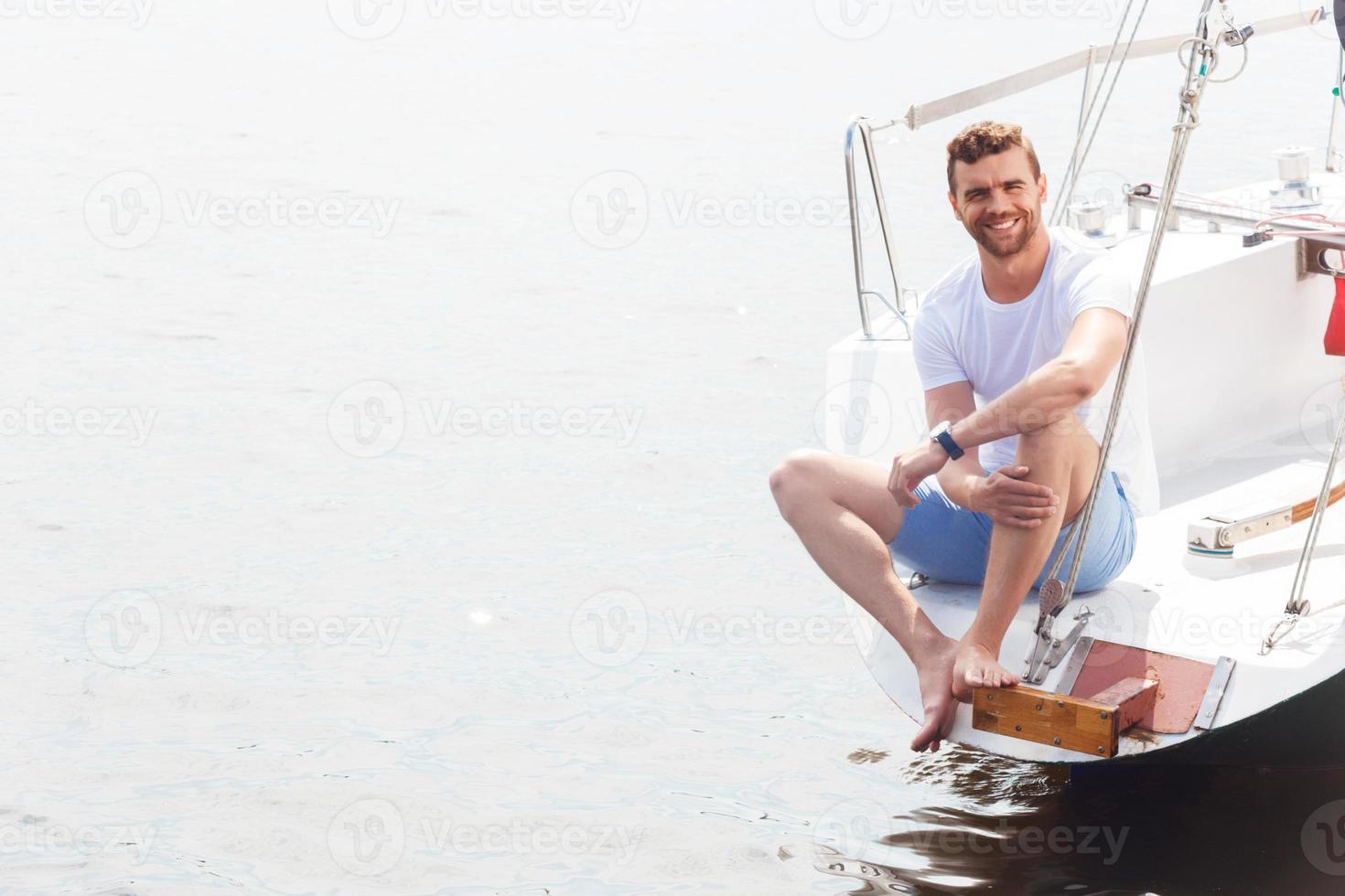 homem agradável, sentado no convés do iate foto