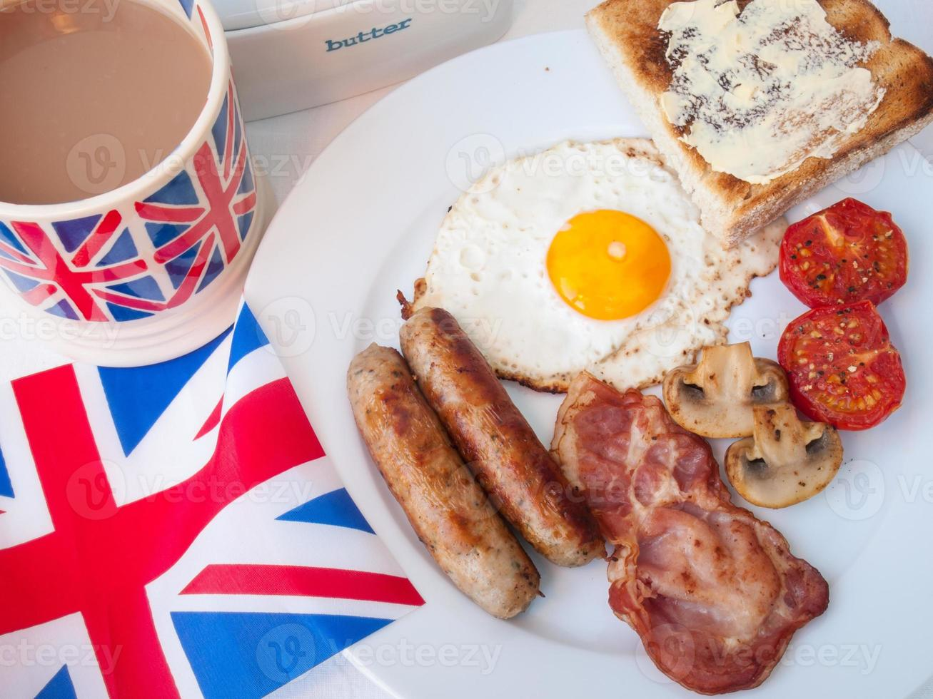 café da manhã frito com uma xícara de chá, torradas e bandeira britânica foto