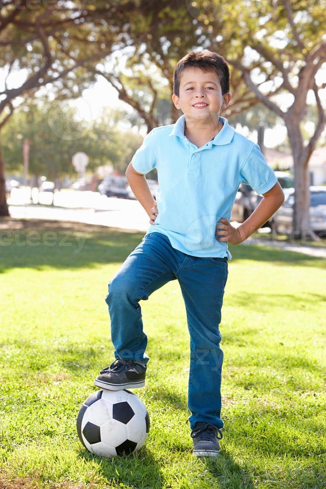 garoto posando com bola de futebol foto