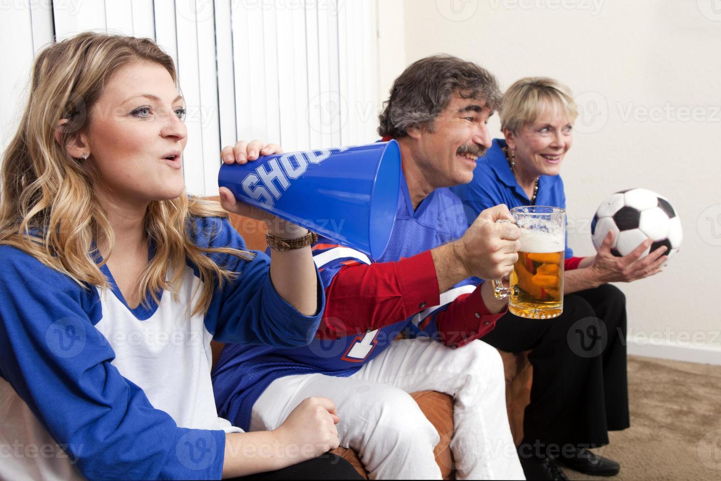 grupo diversificado de familiares e amigos assistindo a um jogo de futebol foto