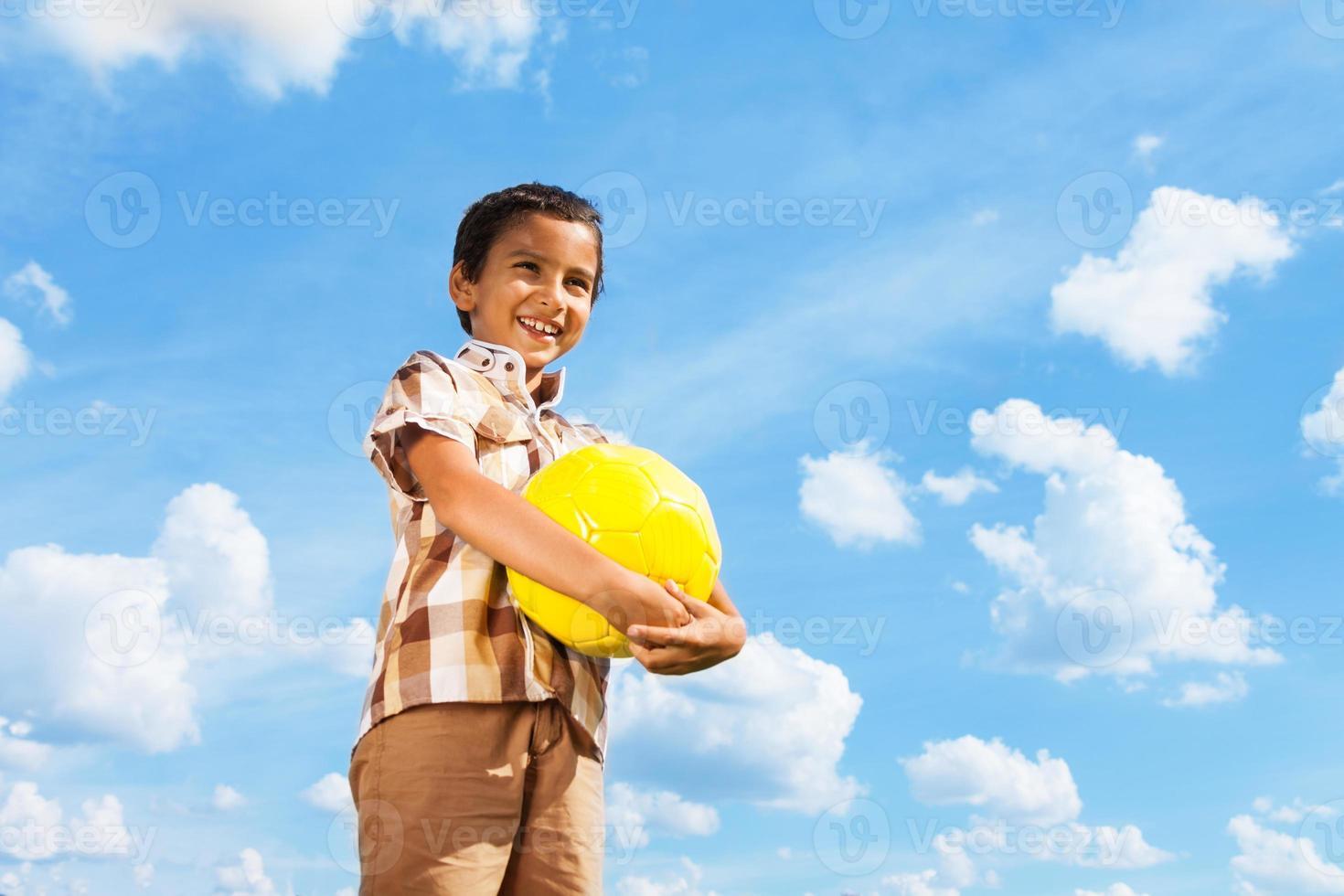 menino de pé com bola de futebol foto