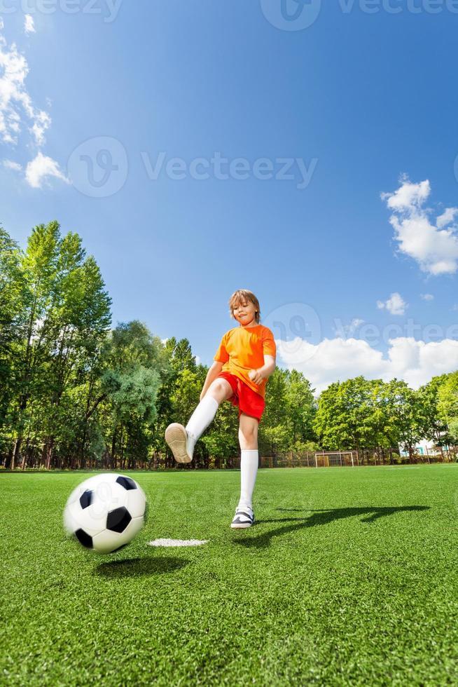 menino chutando futebol com uma perna foto