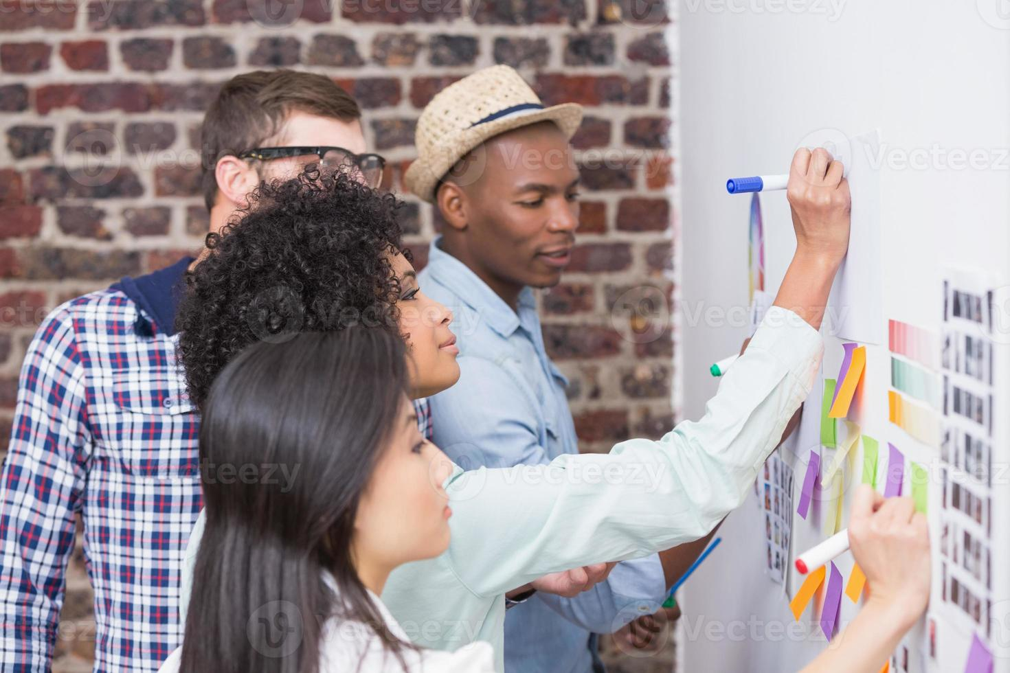 equipe olhando notas autoadesivas na parede foto