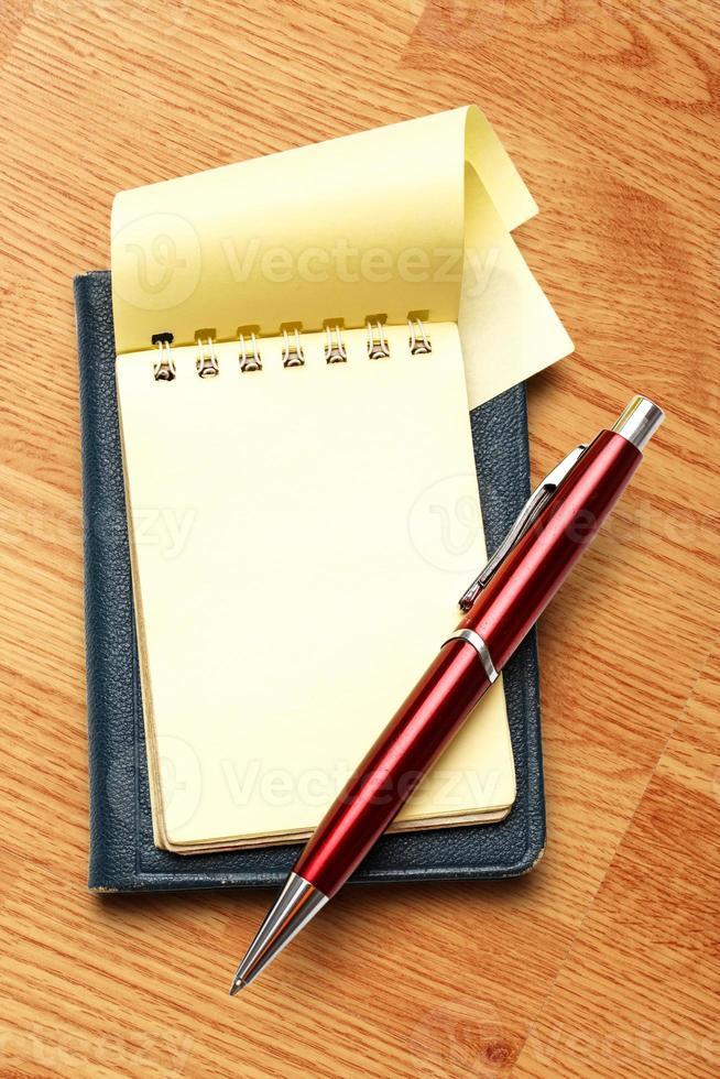 bloco de notas em branco amarelo com caneta foto