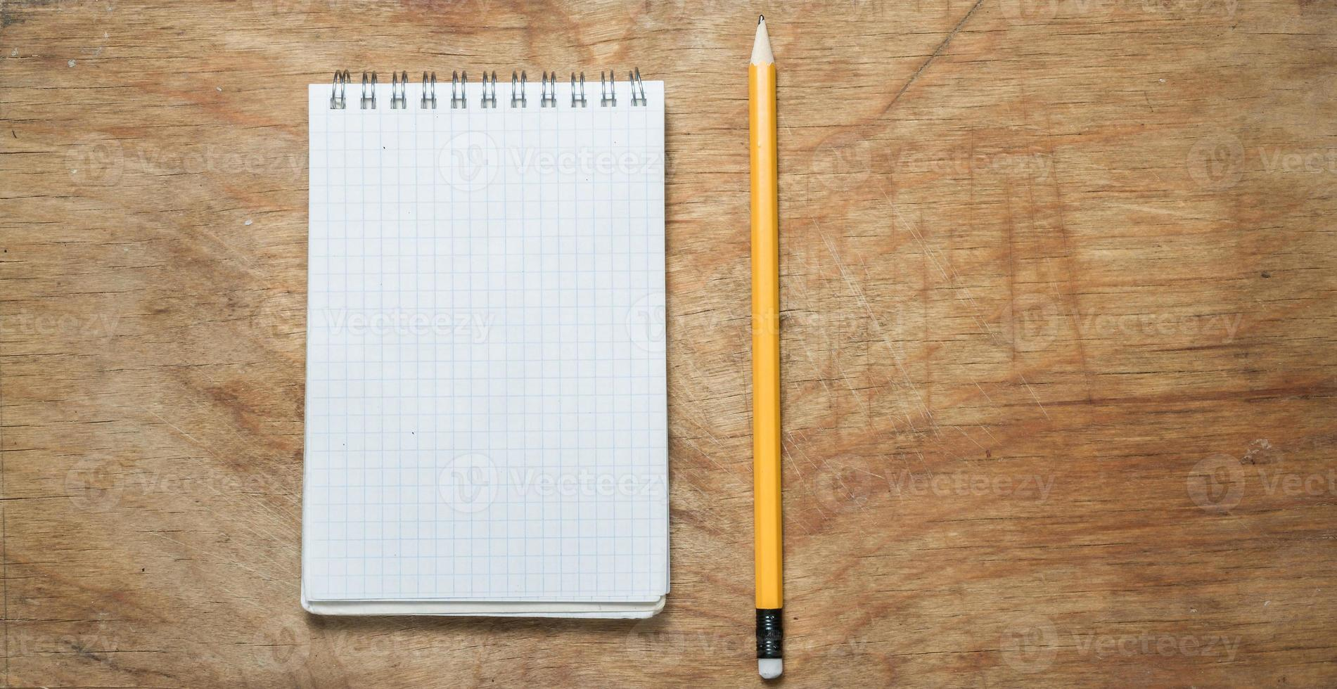lápis e bloco de notas em uma velha mesa rústica. foto