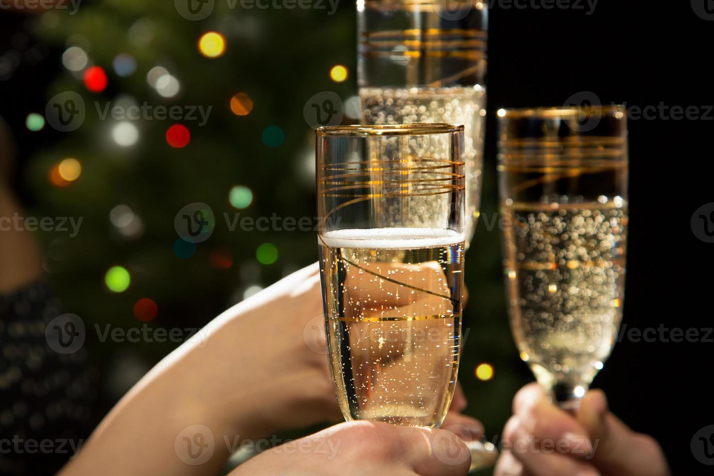 mãos de pessoas com copos de cristal cheios de champanhe foto