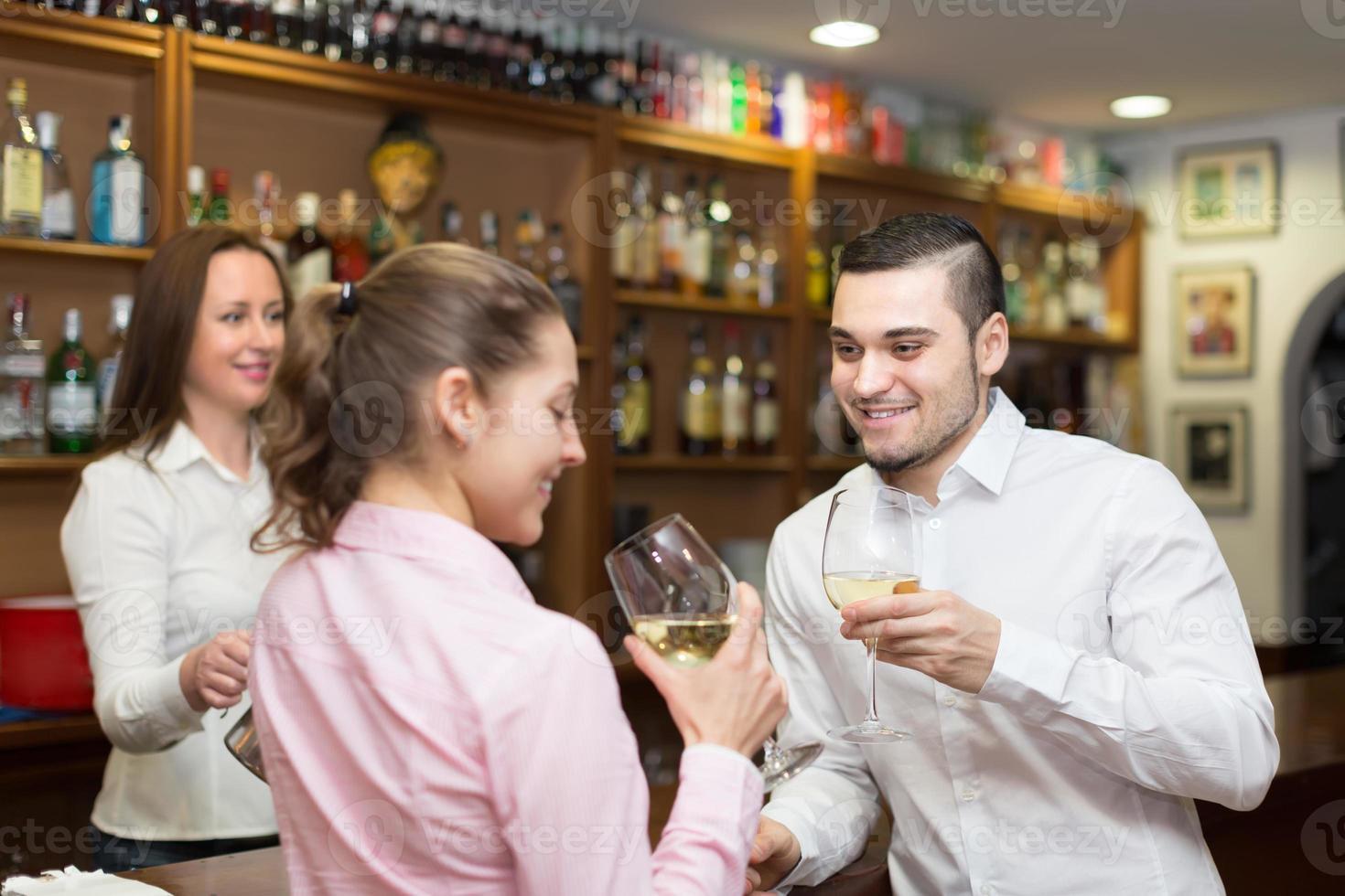 jovem casal com vinho no bar foto