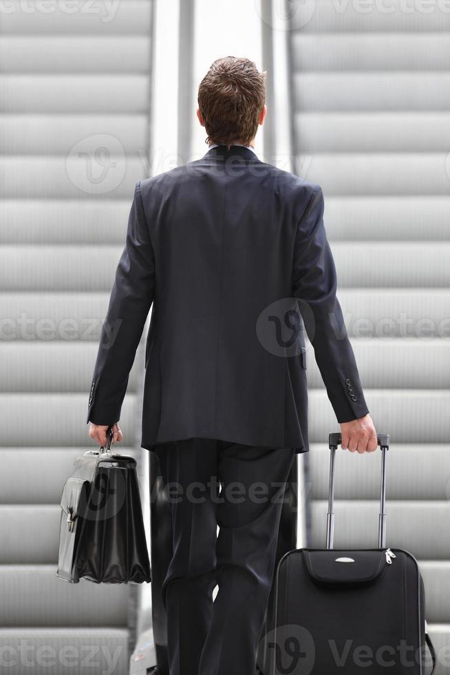 empresário na escada rolante com saco e carrinho foto