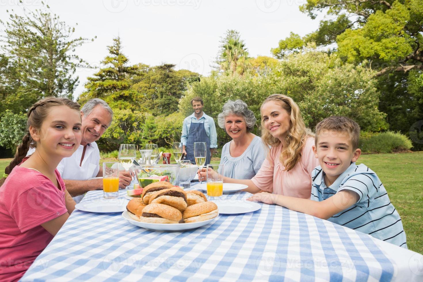 sorrindo a família estendida esperando churrasco sendo cozido por gordura foto