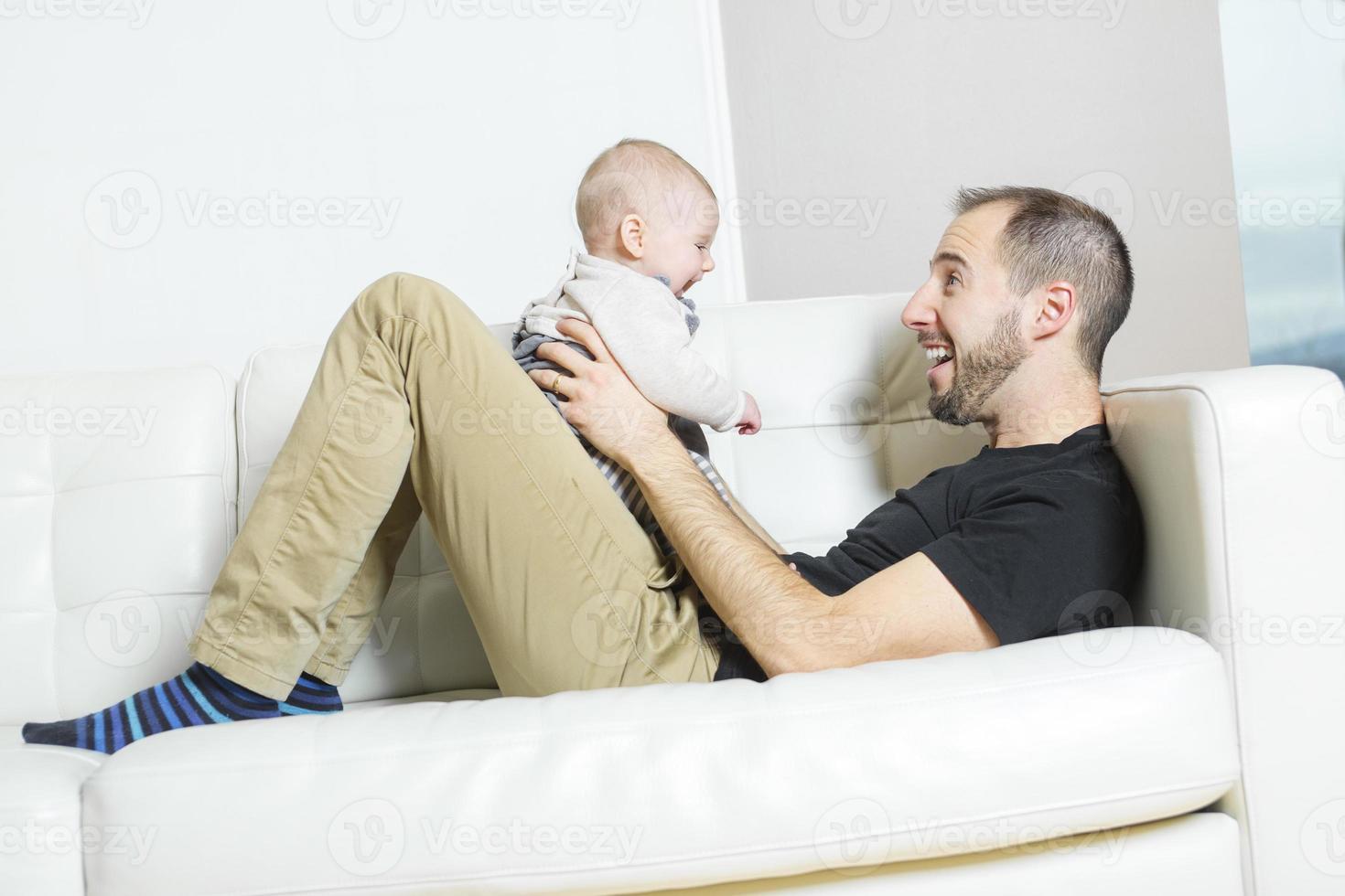 pai com bebê no sofá, tendo um bom tempo foto