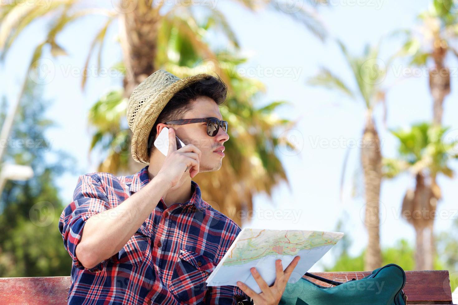 jovem viajante masculino falando no celular e segurando o mapa foto