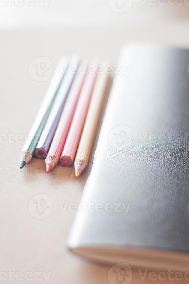 lápis de cor com caderno preto foto