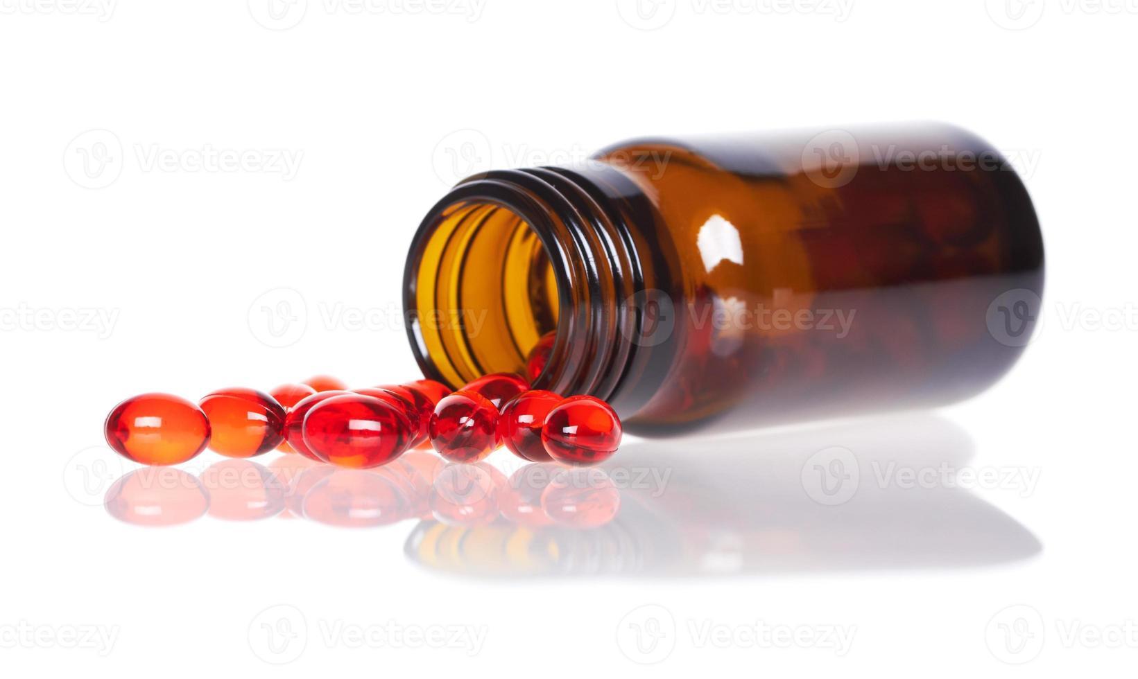 pílulas vermelhas um frasco de comprimidos foto