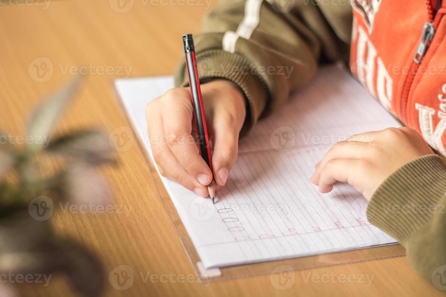 aluno da primeira série escreve cartas em um caderno foto