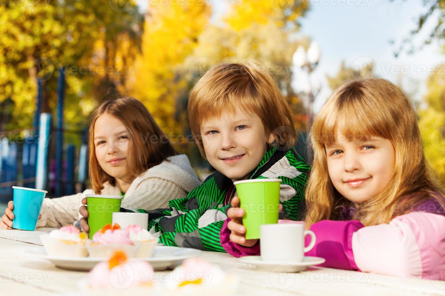 crianças felizes com xícaras de chá sentado do lado de fora foto