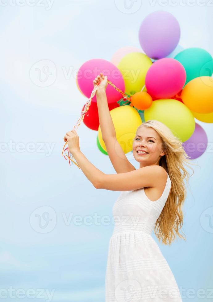 mulher sorridente com balões coloridos lá fora foto