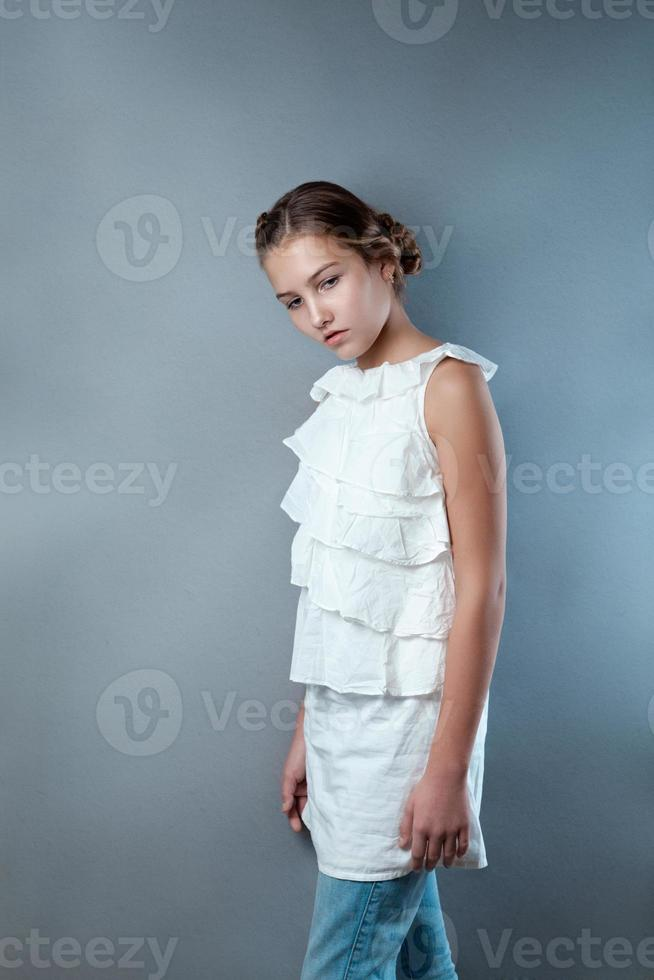 retrato de uma menina bonita em fundo cinza foto