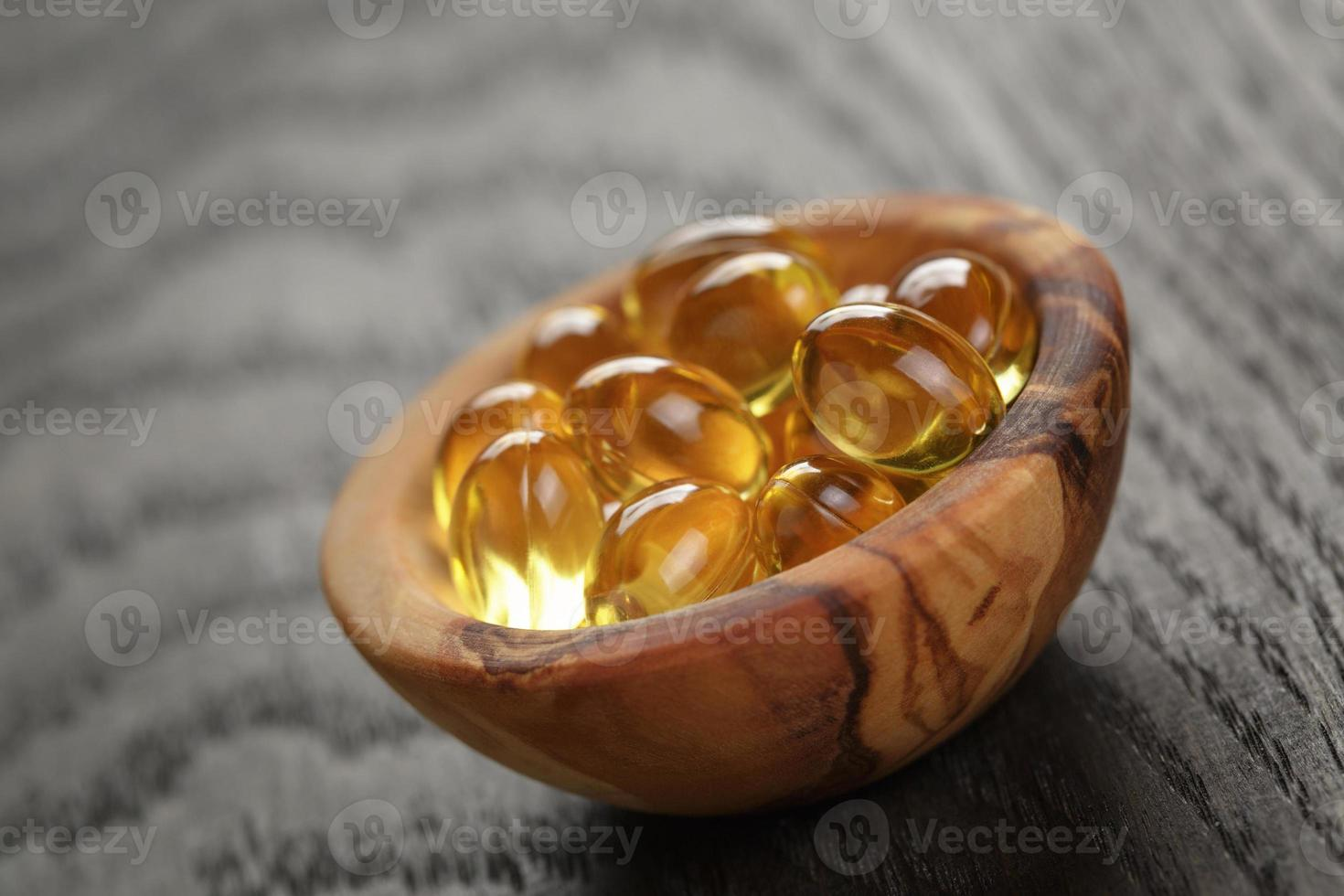 cápsulas de óleo de peixe em uma tigela de madeira na mesa de madeira foto