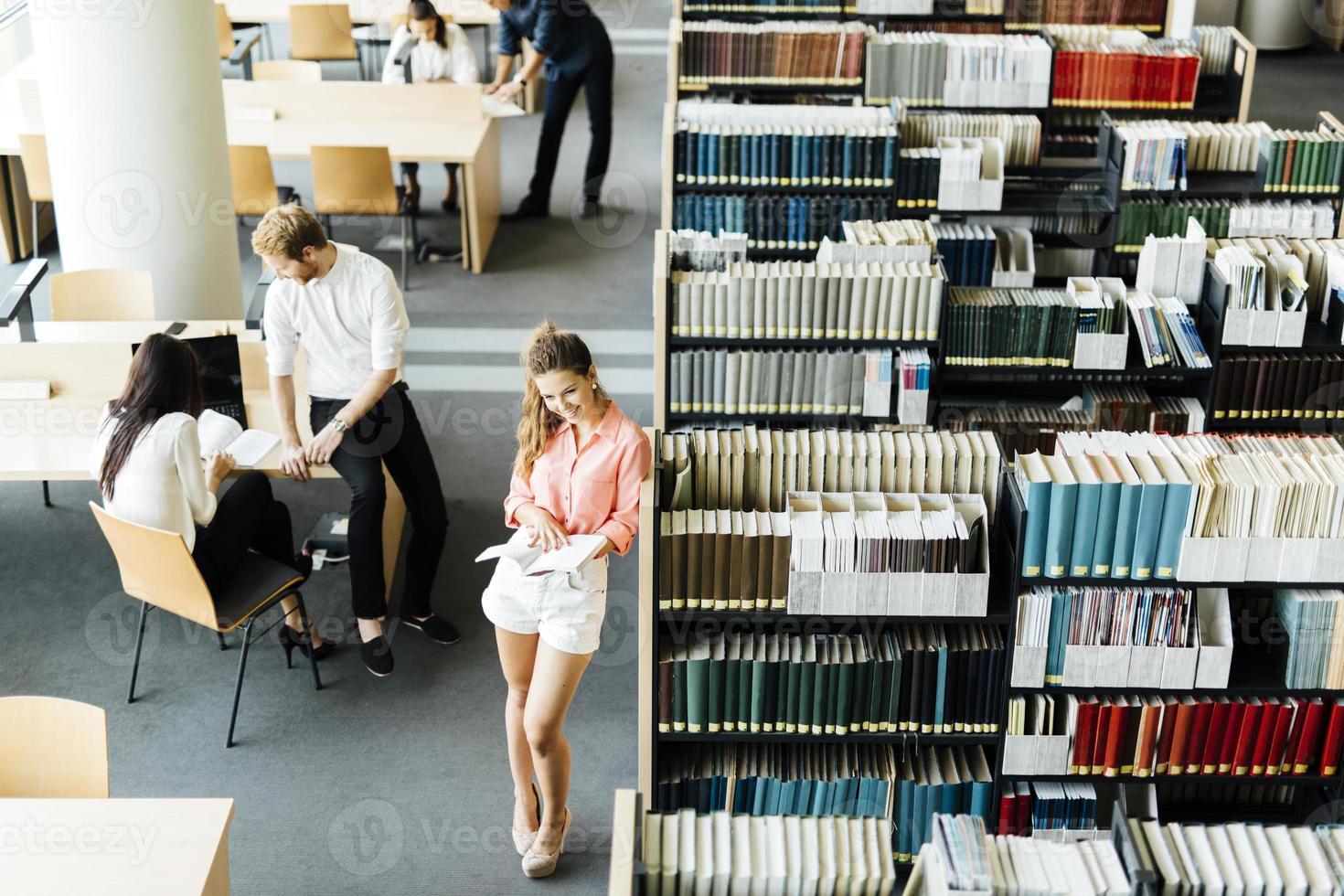 grupo de estudantes estudando em uma biblioteca foto