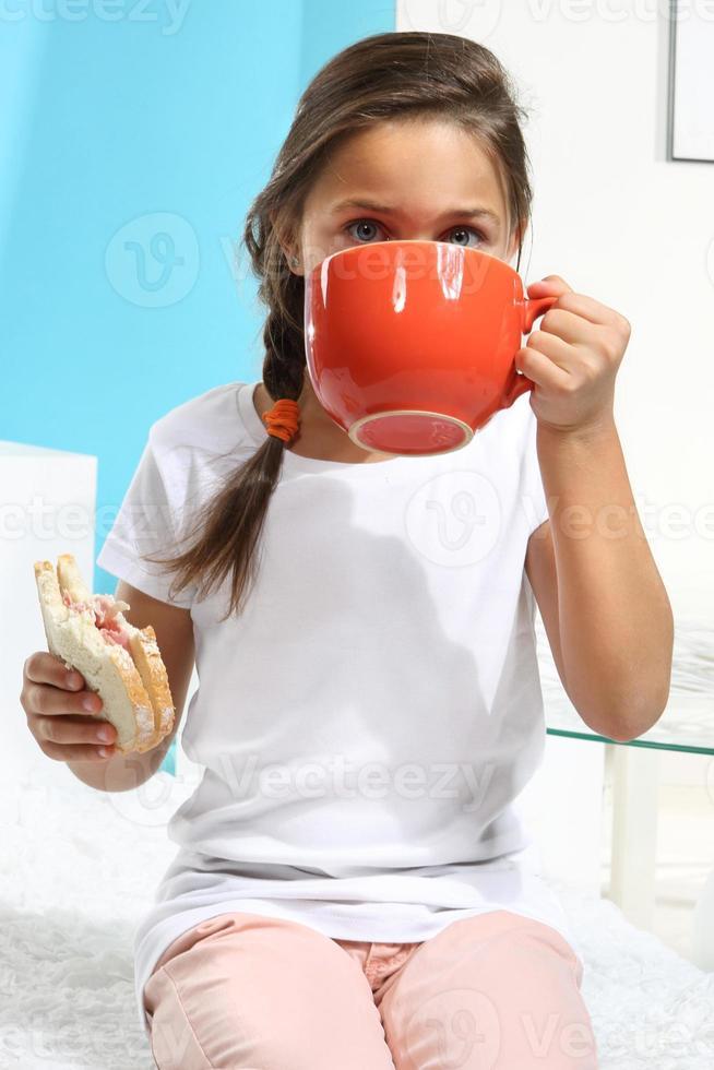 menina bebe chá foto