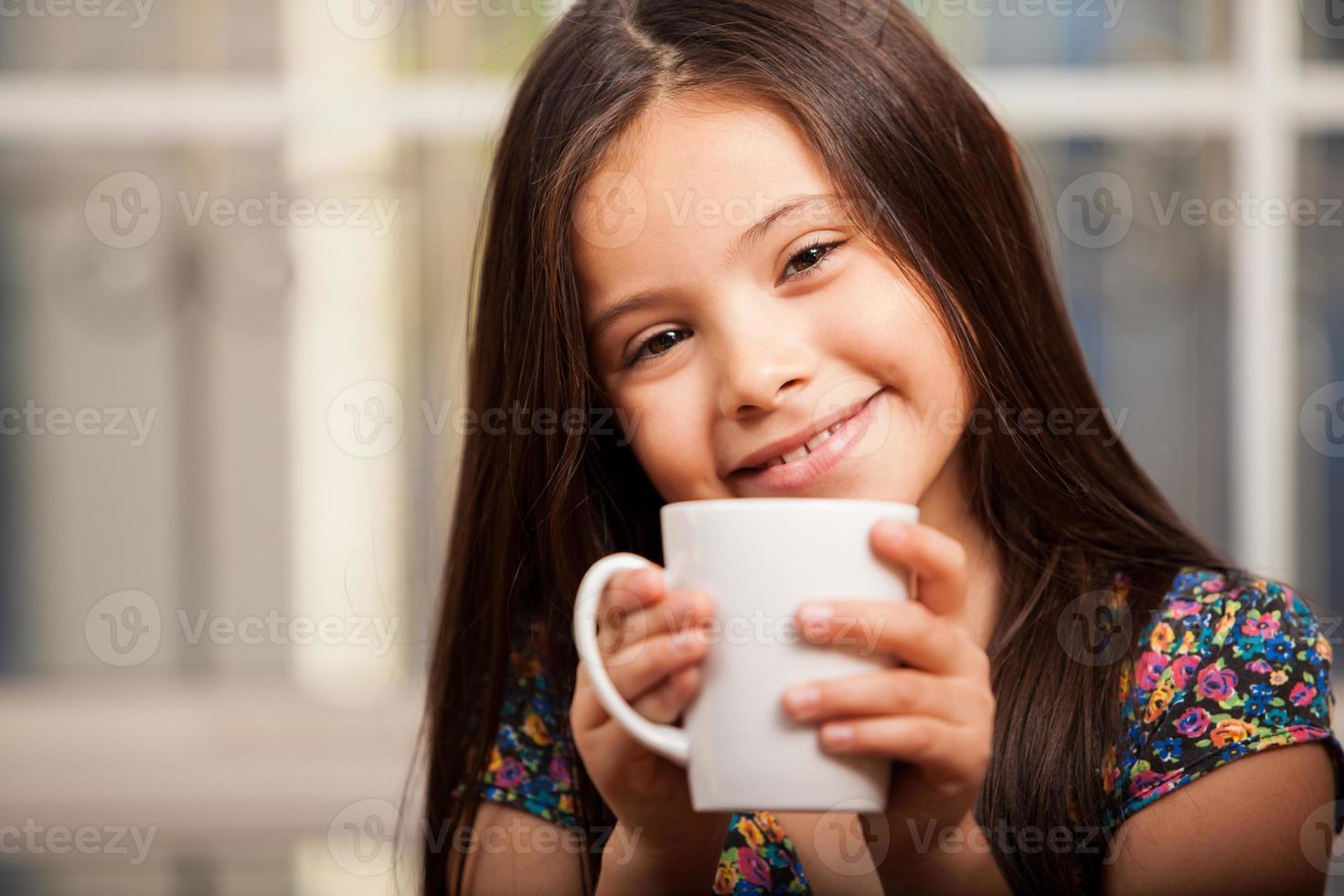 menina feliz bebendo chocolate foto