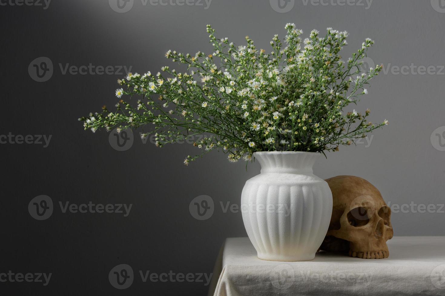 natureza morta com flores em vaso e caveira foto