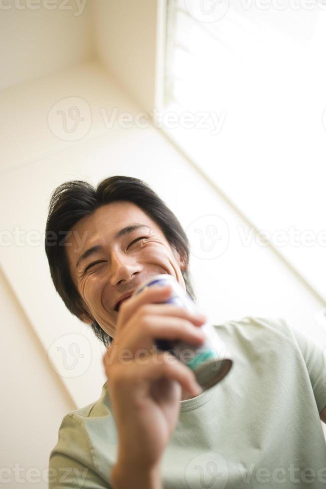 homem rindo com bebida enlatada foto