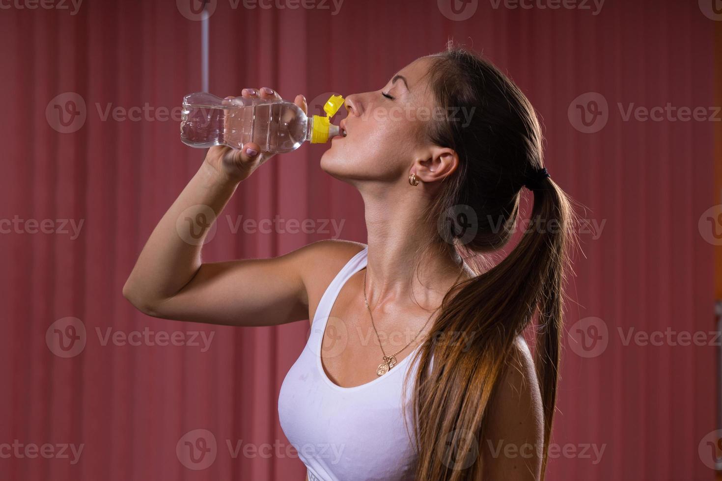mulher atlética água potável sensualmente foto