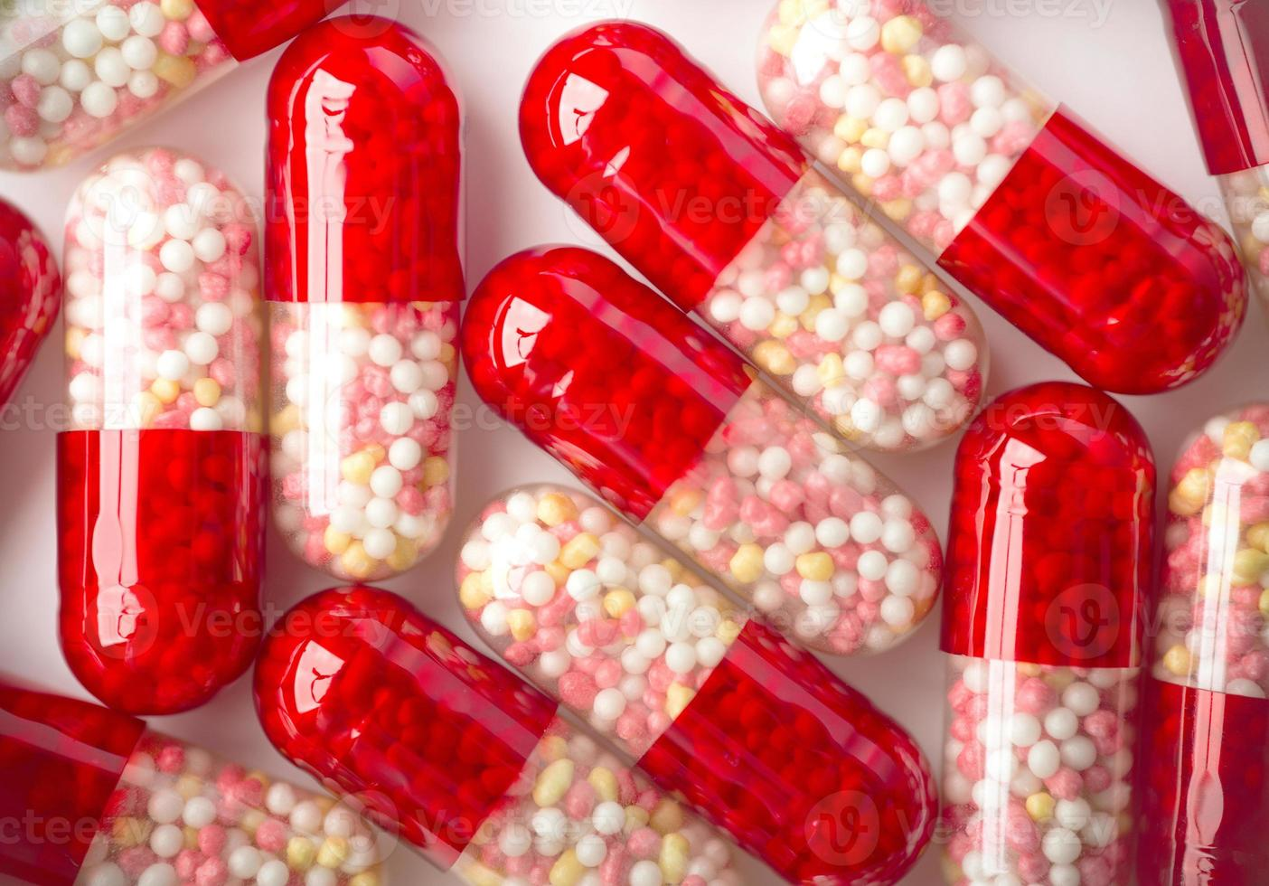 Feche acima das cápsulas vermelhas sobre fundo branco. foto