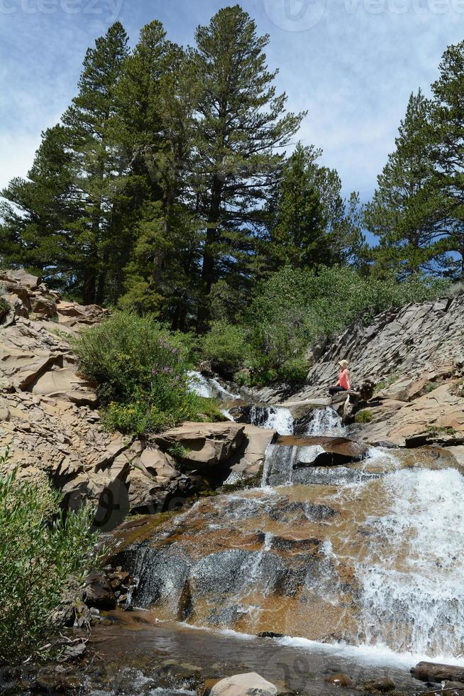 mulher sentada perto de uma cachoeira foto