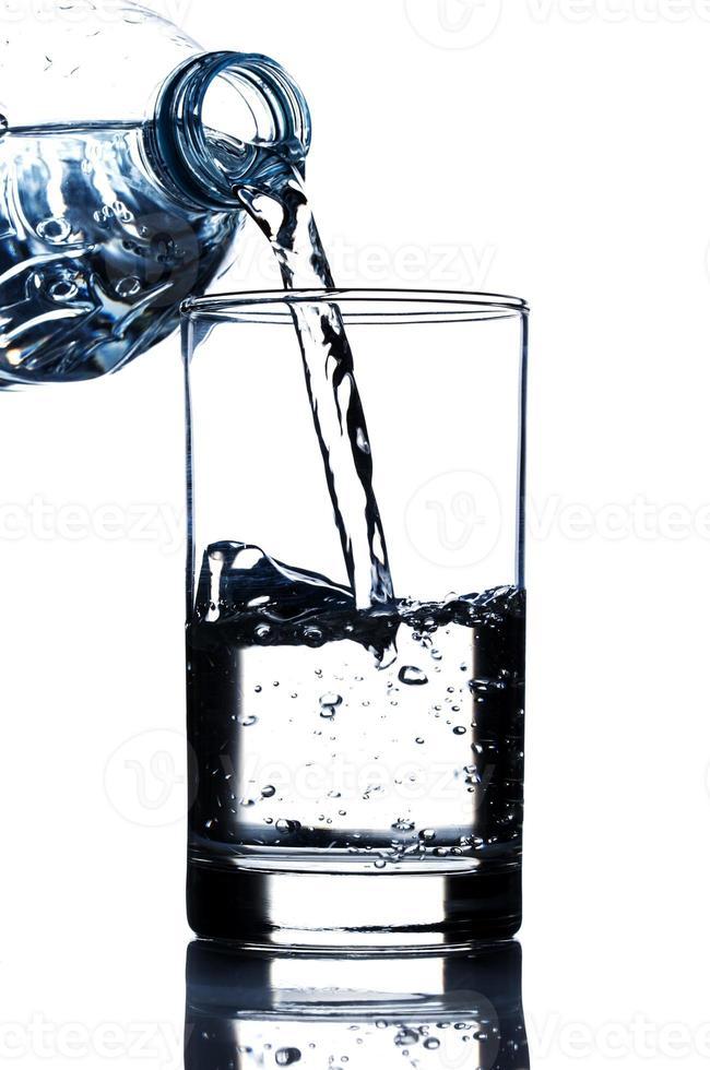 água potável derramando em vidro foto